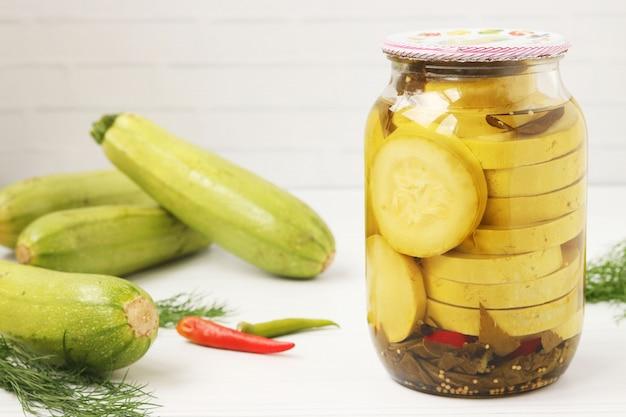 Zucchine in un barattolo, situato su uno sfondo bianco. sullo sfondo sono disposte le zucchine