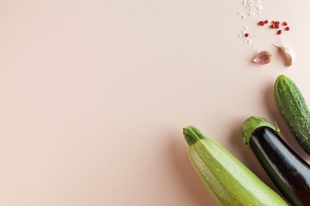 Zucchine, melanzane e cetrioli su uno sfondo rosa. minimalismo. concetto di raccolta, agricoltura. verdure.