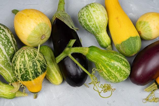 Zucchine, melanzane si trovano su uno sfondo grigio chiaro, raccolta