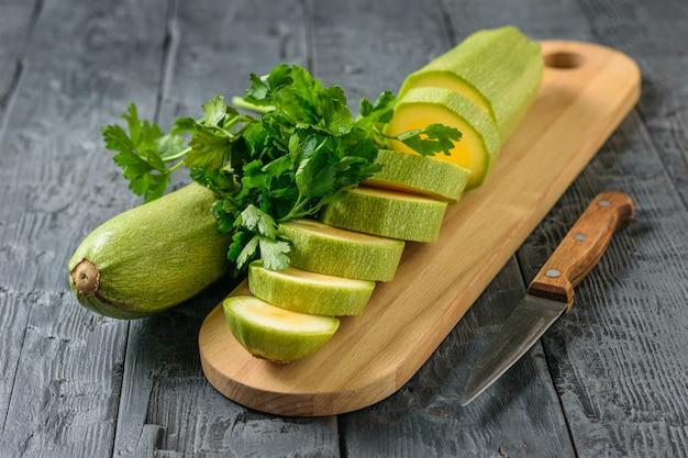 Zucchine su un tagliere con prezzemolo e un coltello su un tavolo di legno.