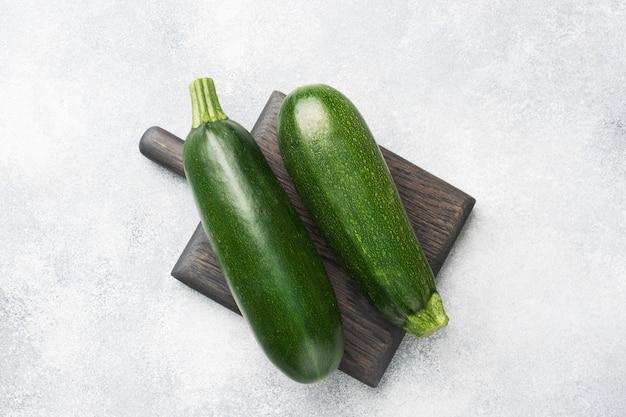 Zucchine verdi fresche su un tagliere. sfondo grigio cemento. copia spazio.