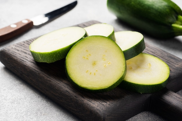 Zucchine verdi fresche tagliate a fette su un tagliere. sfondo grigio cemento. avvicinamento.