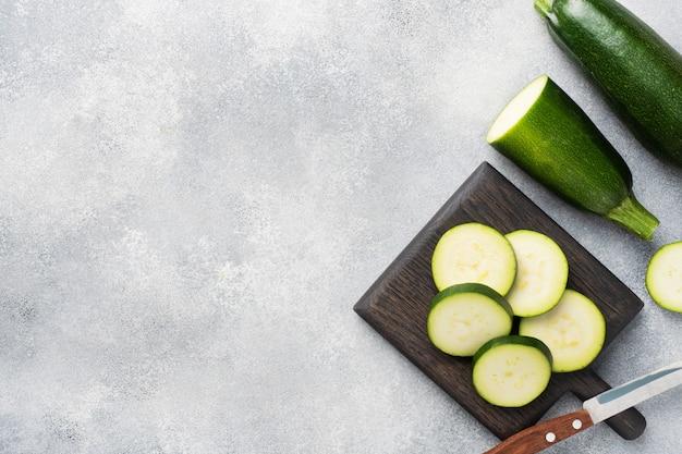 Zucchine verdi fresche tagliate a fette su un tagliere. sfondo grigio cemento. copia spazio.