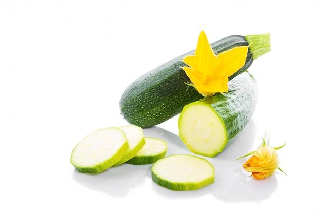 Zucchini o zucca verde con foglie verdi e fiori isolati su bianco