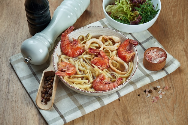 Zuppa al brodo con spaghetti e gamberi, calamari in ciotola di ceramica bianca sul tavolo di legno. gustosa zuppa di pesce. cibo piatto disteso