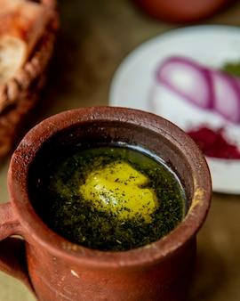 Zuppa cotta in una pentola di terracotta e servita con erbe