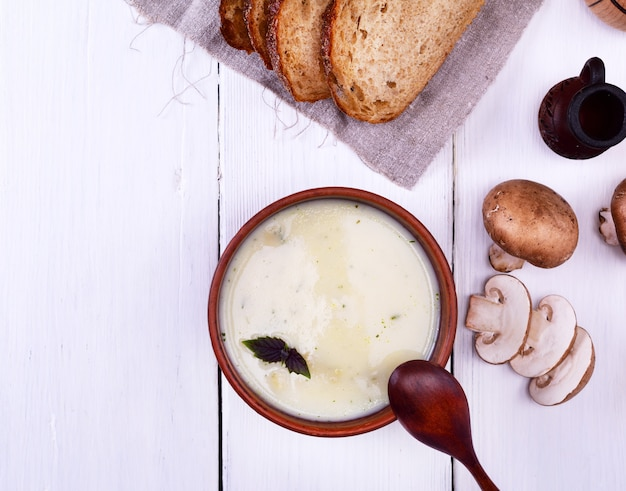 Zuppa cremosa con funghi in un piatto di argilla rotonda