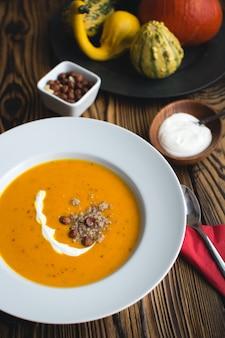 Zuppa cremosa di zucca con crema e nocciole