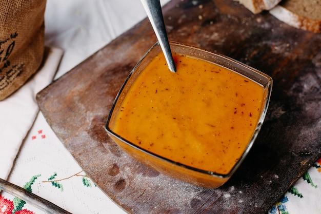 Zuppa d'arancia verdura ricca di vitamine deliziose salate pepate sulla scrivania rustica in legno marrone