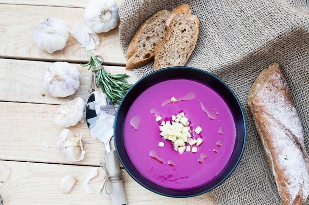 Zuppa di barbabietole con aglio e rosmarino e baguette di segale su una superficie di legno nera