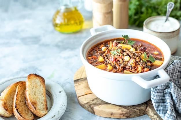 Zuppa di carne macinata spessa con pomodori, fagioli, ceci e verdure. cena salutare. copia spazio