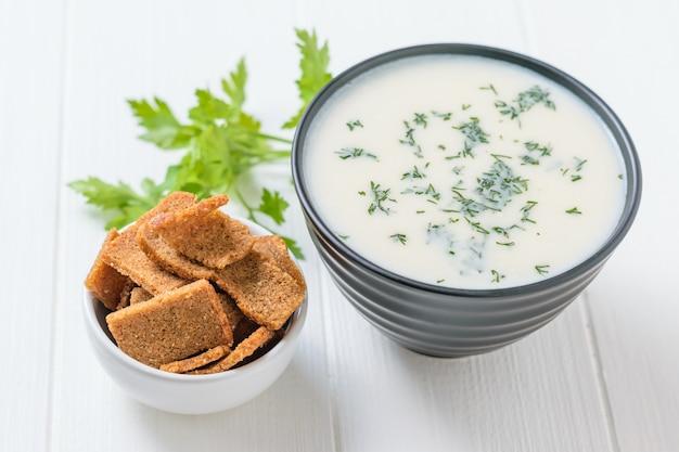Zuppa di cavolfiore crema con erbe e cracker su un tavolo bianco.