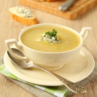 Zuppa di cipolle fatta in casa con sedano e formaggio blu su fondo di legno