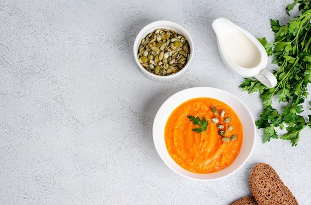 Zuppa di crema autunnale vegetariana di zucche e carote con semi e prezzemolo, piatto laici
