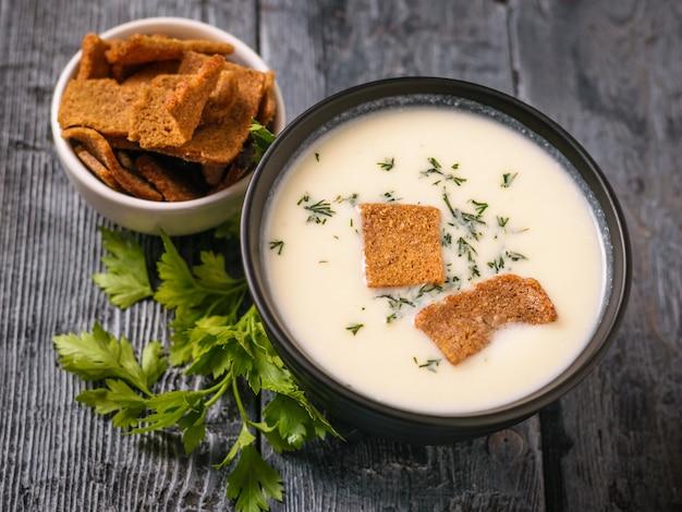 Zuppa di crema di cavolfiore con erbe e cracker su un tavolo nero.