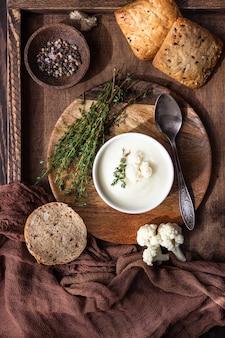 Zuppa di crema di cavolfiore guarnire con cavolfiore fresco, timo e pane in una ciotola di ceramica bianca.