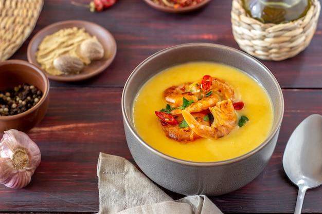Zuppa di crema di formaggio con gamberi alla griglia su uno sfondo di legno.