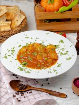 Zuppa di crema di lenticchie con patate e salsa di pomodoro e verdure, servita con lavash in piatto bianco