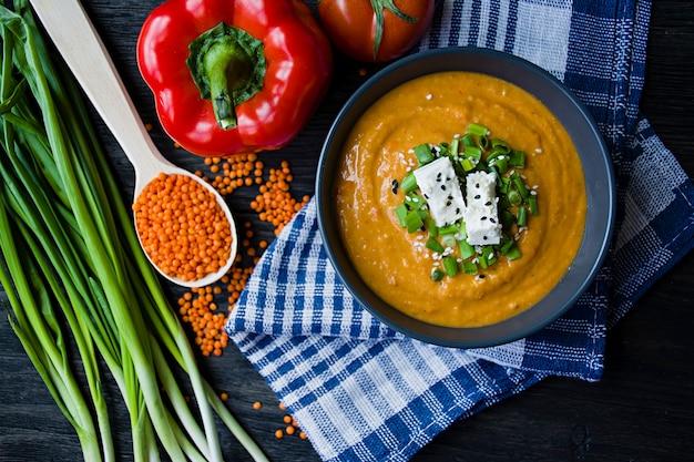 Zuppa di crema di lenticchie rosse decorata con verdure fresche e verdure.