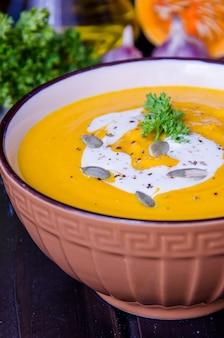 Zuppa di crema di zucca con lenticchie rosse e carota in una ciotola su un fondo di legno