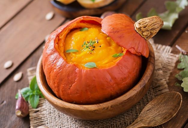 Zuppa di crema di zucca con peperoni ed erbe aromatiche in una zucca