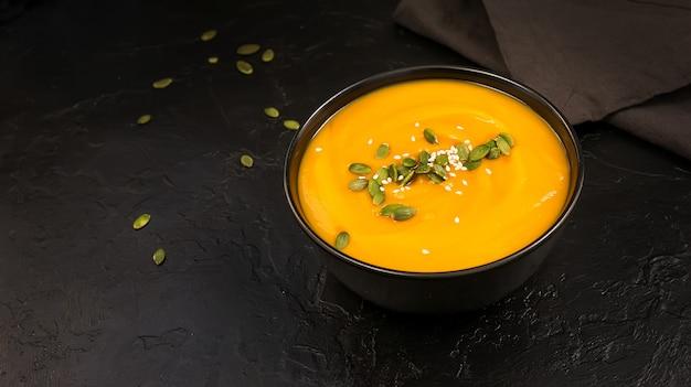 Zuppa di crema di zucca con semi in una ciotola nera
