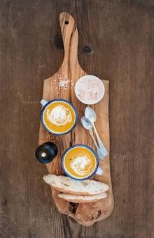 Zuppa di crema di zucca fatta in casa in tazze di smalto con erbe e fette di pane fresco su tavola da portata verde oliva su legno rustico