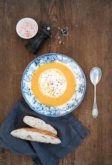 Zuppa di crema di zucca fatta in casa nel piatto di porcellana con spezie e fette di pane fresco sopra sopra in legno rustico