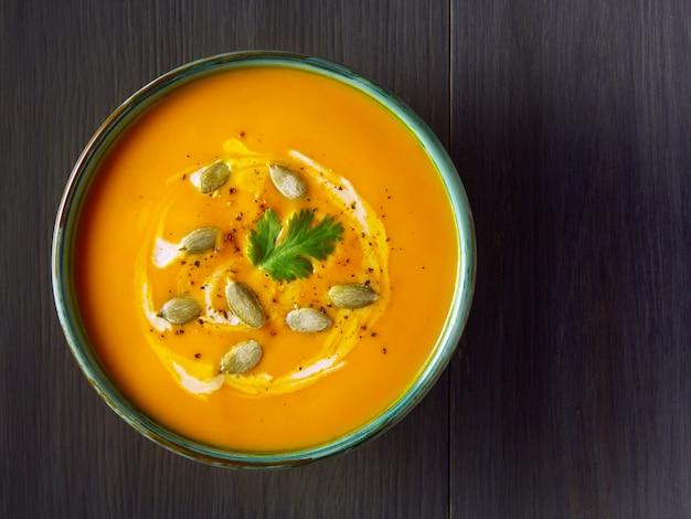 Zuppa di crema di zucca in una ciotola con semi di zucca, prezzemolo e crema sul tavolo di legno.