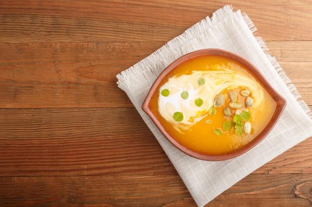 Zuppa di crema di zucca tradizionale con semi in ciotola di argilla su un fondo di legno marrone con tovagliolo di lino. vista dall'alto, copia spazio.