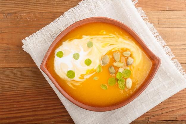 Zuppa di crema di zucca tradizionale con semi in ciotola di argilla su un fondo di legno marrone con tovagliolo di lino
