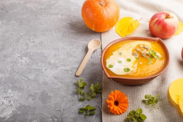 Zuppa di crema di zucca tradizionale con semi in ciotola di argilla su uno sfondo di cemento grigio con tessuto di lino