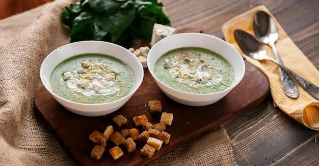 Zuppa di crema verde di spinaci e broccoli. con l'aggiunta di parmigiano e gorgonzola ai crostini. una superficie di legno.