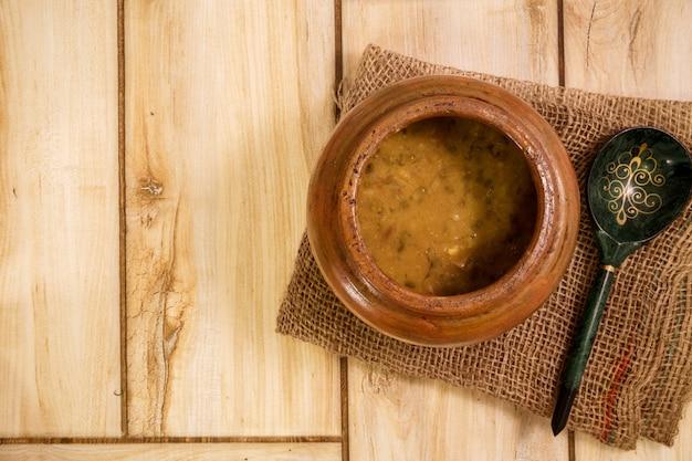 Zuppa di fagioli in un vaso tradizionale su un tavolo di legno. vista dall'alto