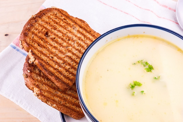 Zuppa di formaggio in un piatto bianco con pane tostato