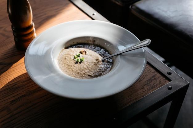 Zuppa di funghi con grouton in zolla bianca con luce solare sul tavolo di legno.