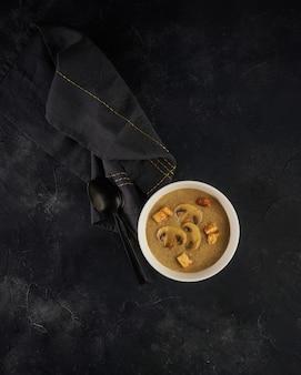 Zuppa di funghi in una ciotola bianca con crostini di pane su sfondo scuro. vista dall'alto con spazio di copia