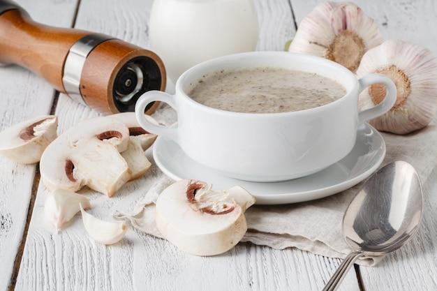Zuppa di fungo in vaso bianco su legno bianco