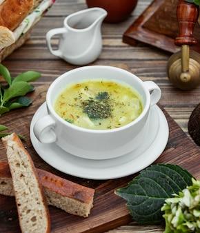 Zuppa di gnocchi di dushbara servita con pane sul tavolo di legno