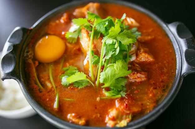 Zuppa di kimchi con uova di gallina crude e tofu bianco, popolare cibo coreano.