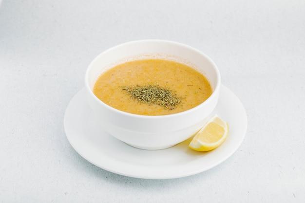 Zuppa di lenticchie con erbe e spezie in ciotola bianca.
