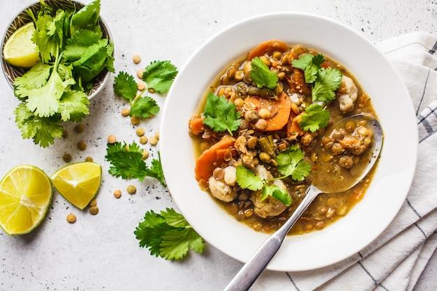 Zuppa di lenticchie con verdure in un piatto bianco, sfondo bianco, vista dall'alto. cibo a base vegetale, mangiare pulito.