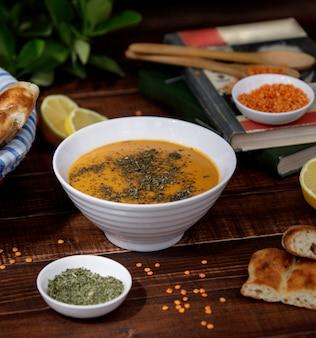 Zuppa di lenticchie di pomodoro con erbe in una ciotola bianca