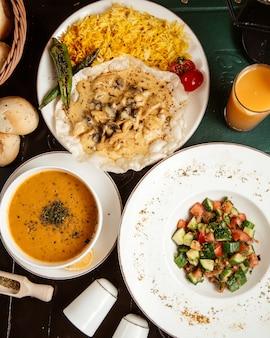Zuppa di lenticchie di primo e secondo piatto con vista dall'alto con insalata greca e piatto principale e succo di frutta sul tavolo