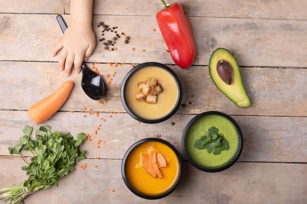 Zuppa di lenticchie rosse, crema di avacado e zuppa di piselli in una scatola, pomodori freschi, prezzemolo
