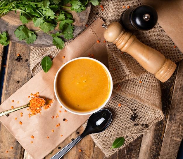 Zuppa di lenticchie rosse in tazza usa e getta servita con verdure verdi.