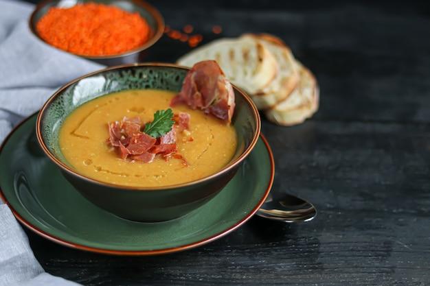Zuppa di lenticchie su un fondo di legno. servito con pancetta affettata ed erbe. nelle vicinanze ci sono pezzi di ciabatta.