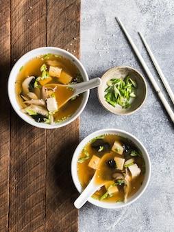 Zuppa di miso giapponese con funghi ostrica in ciotole bianche con un cucchiaio e le bacchette bianche