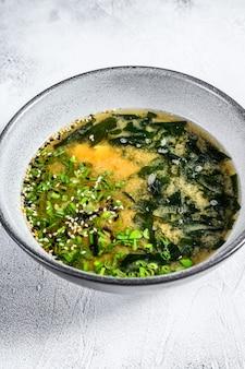 Zuppa di miso giapponese in una ciotola bianca. sfondo bianco. vista dall'alto