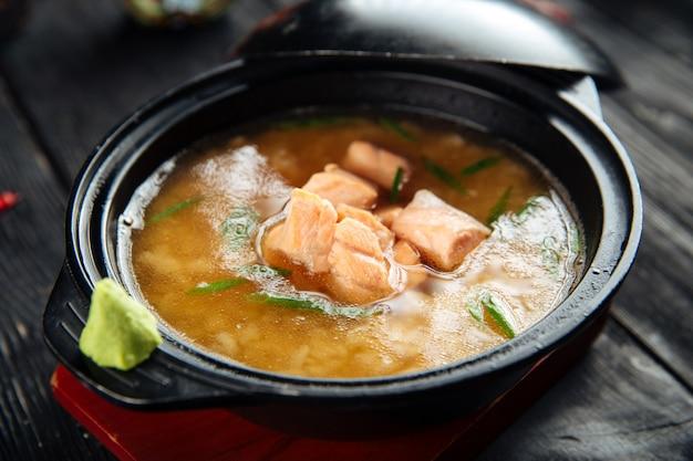 Zuppa di miso ishikari con salmone in una ciotola nera